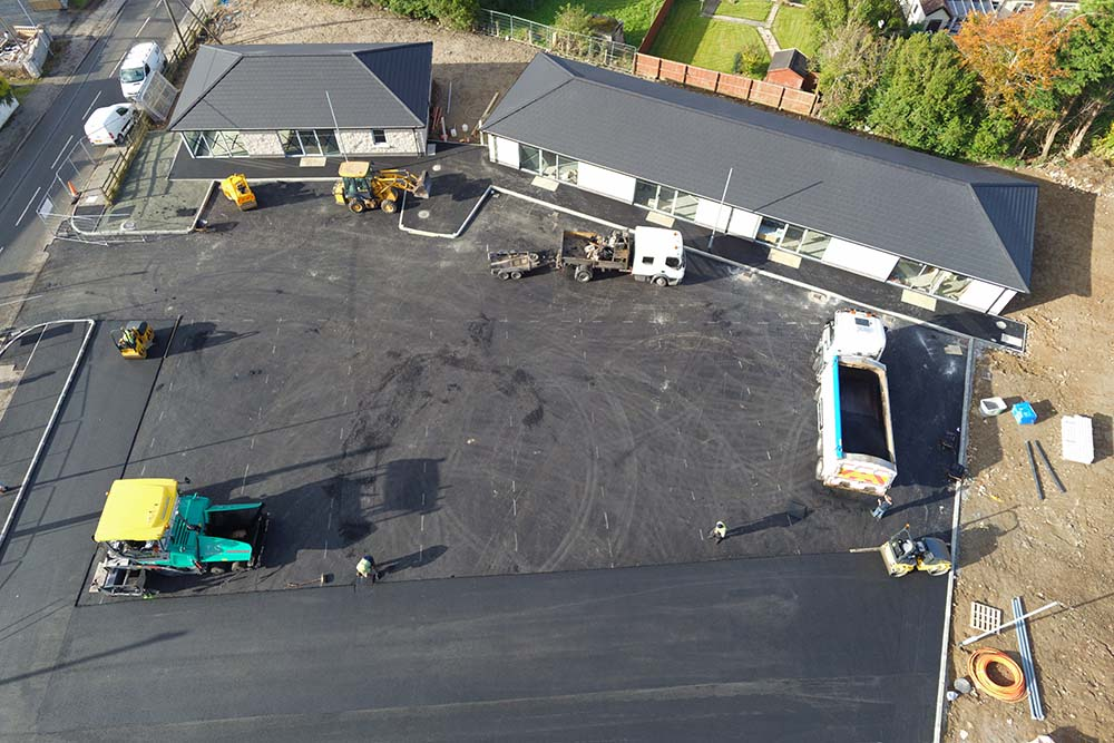Drone shot of construction workers tarmacing carpark